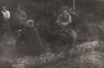Rozmowy przy ognisku, od prawej stoją naganiacz, Jan Boligłowa, Józef Bednarz, Tadeusz Bodziony, Stanisław Piksa. Na pniu od prawej siedzą Franciszek Kowal, myśliwy nierozpoznany i Antoni Duńczyk.